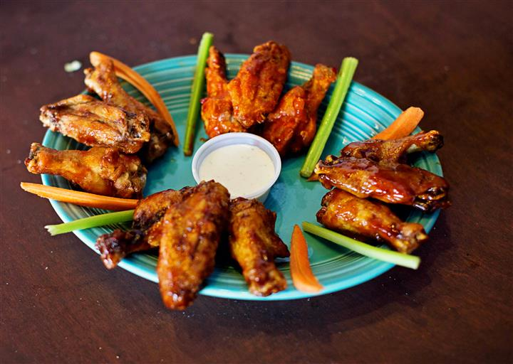 Traditional wings with celery and carrot sticks on a blue plate.