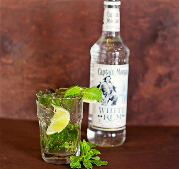 Small glass with a lime wedge and mint leaves with a bottle of white rum Captain Morgan.
