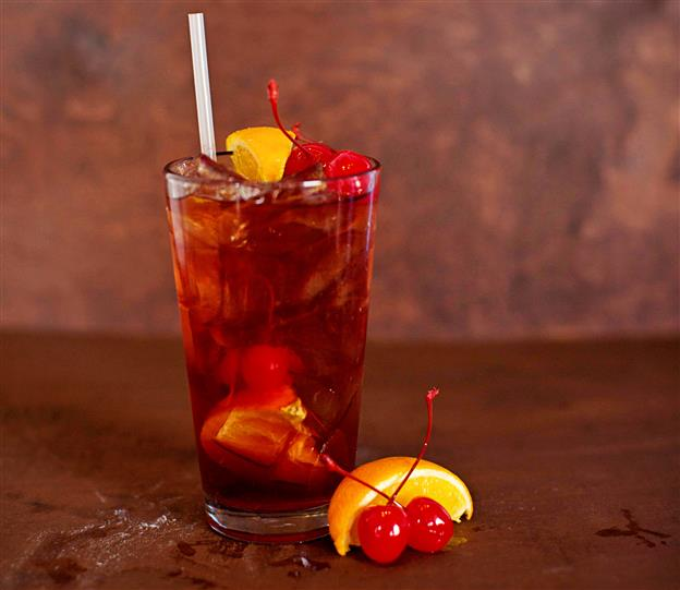 Red cocktail with orange wedges and cherries.
