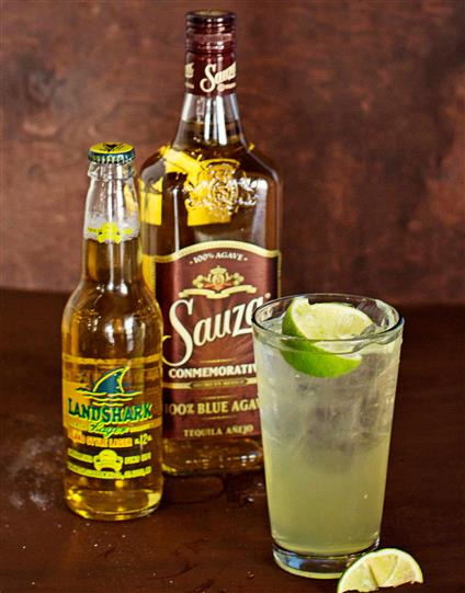 Landshark beer with a bottle of tequila and a pint size cocktail with a lime wedge.