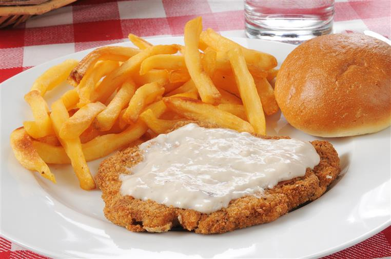 Chicken fried steak with a side of french fries