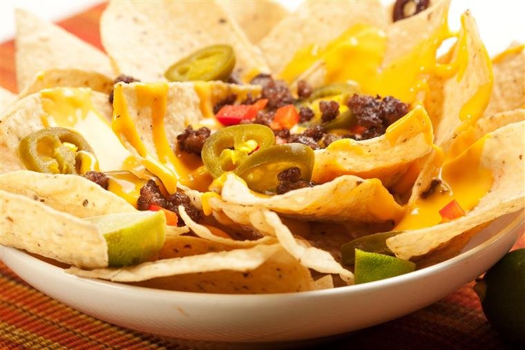 Beef nachos topped with peppers, nacho cheese, and jalapenos