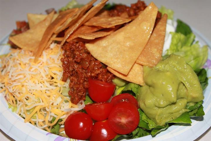 Nachos along side cheese, guacamole, tomatoes, ground beef, and lettuce