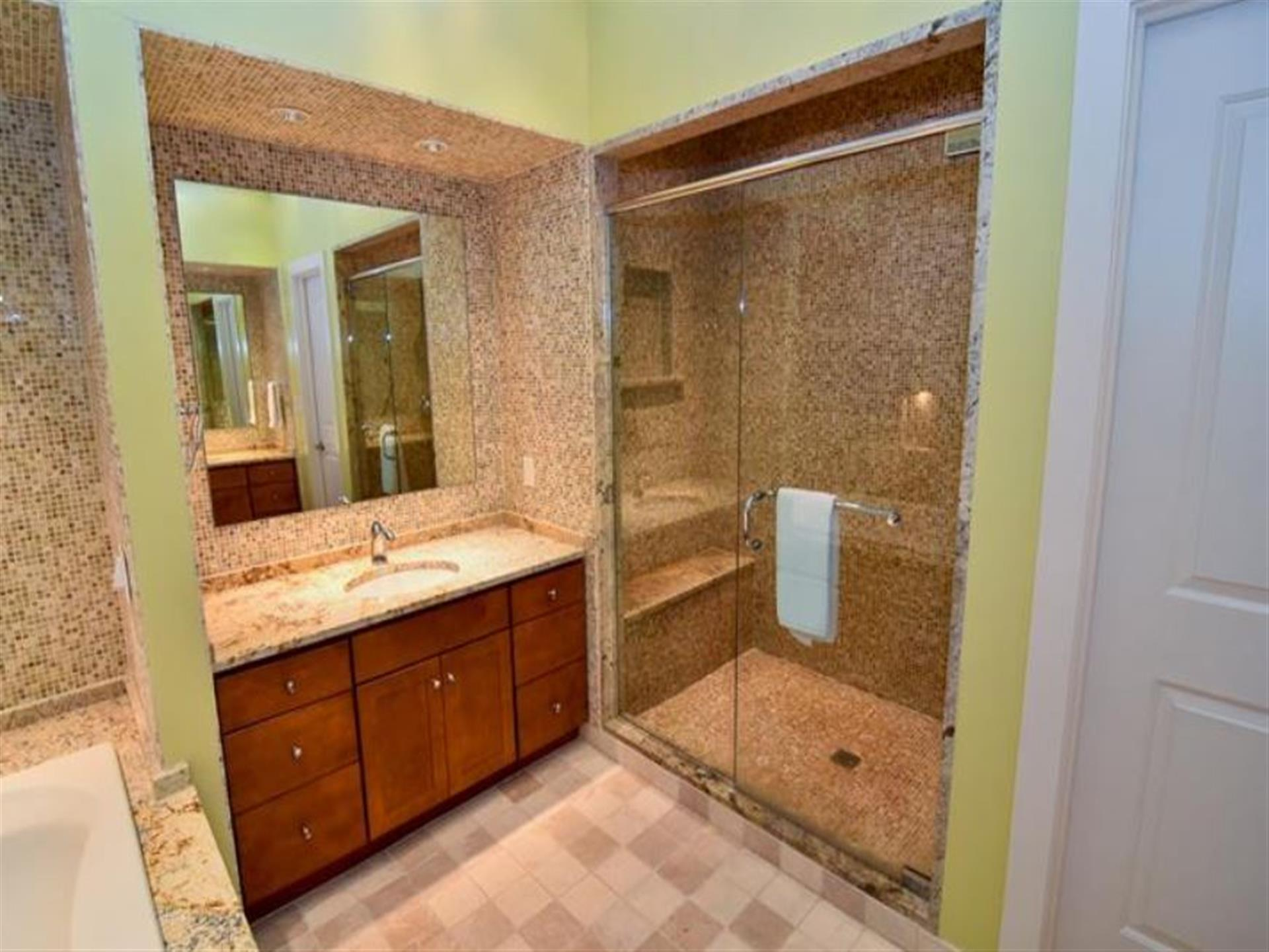 View of a bathroom with a mirror, counter with a sink as well as a shower