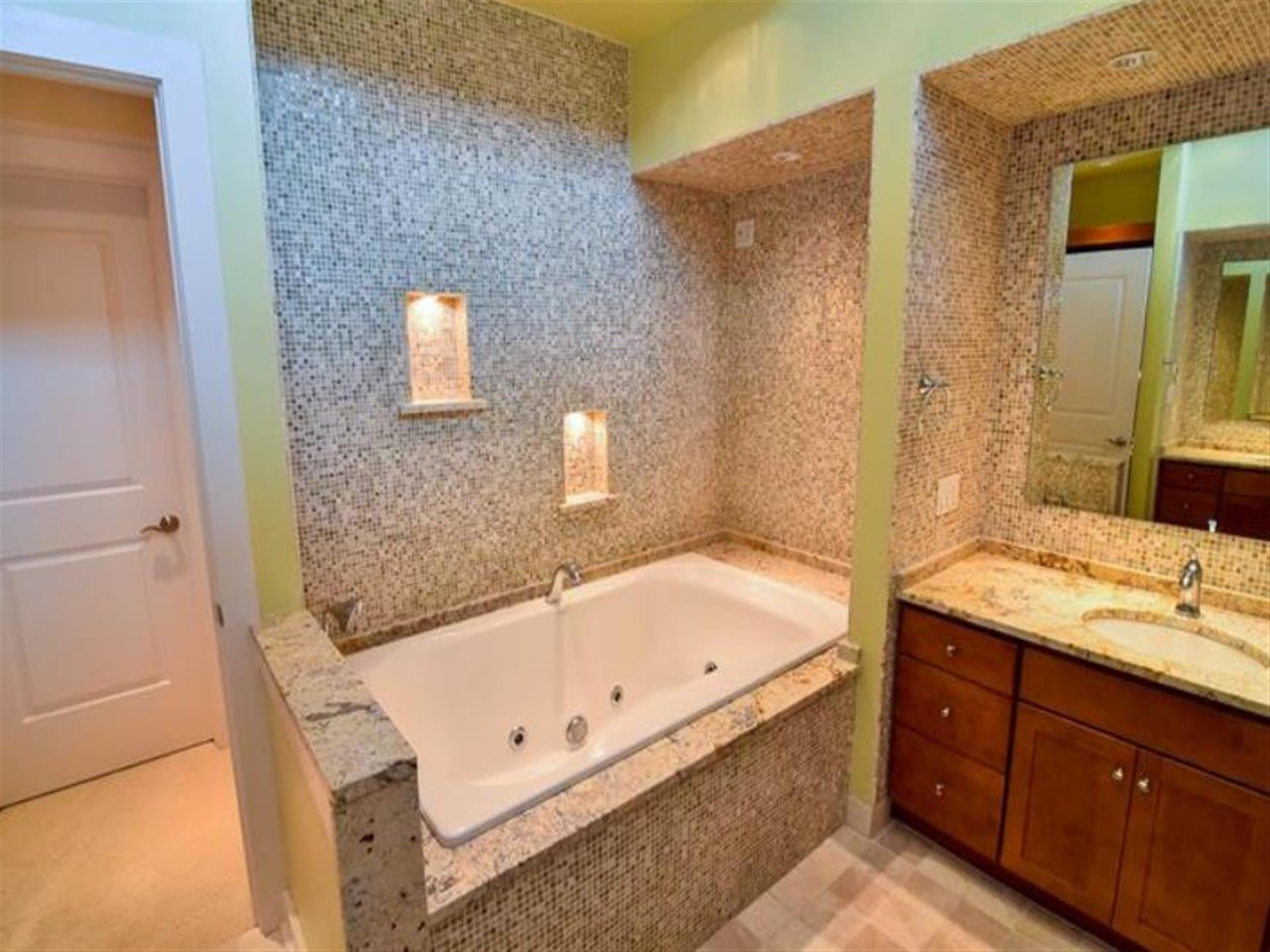 One bathroom with speckled tiles, a tub and a counter with a sink