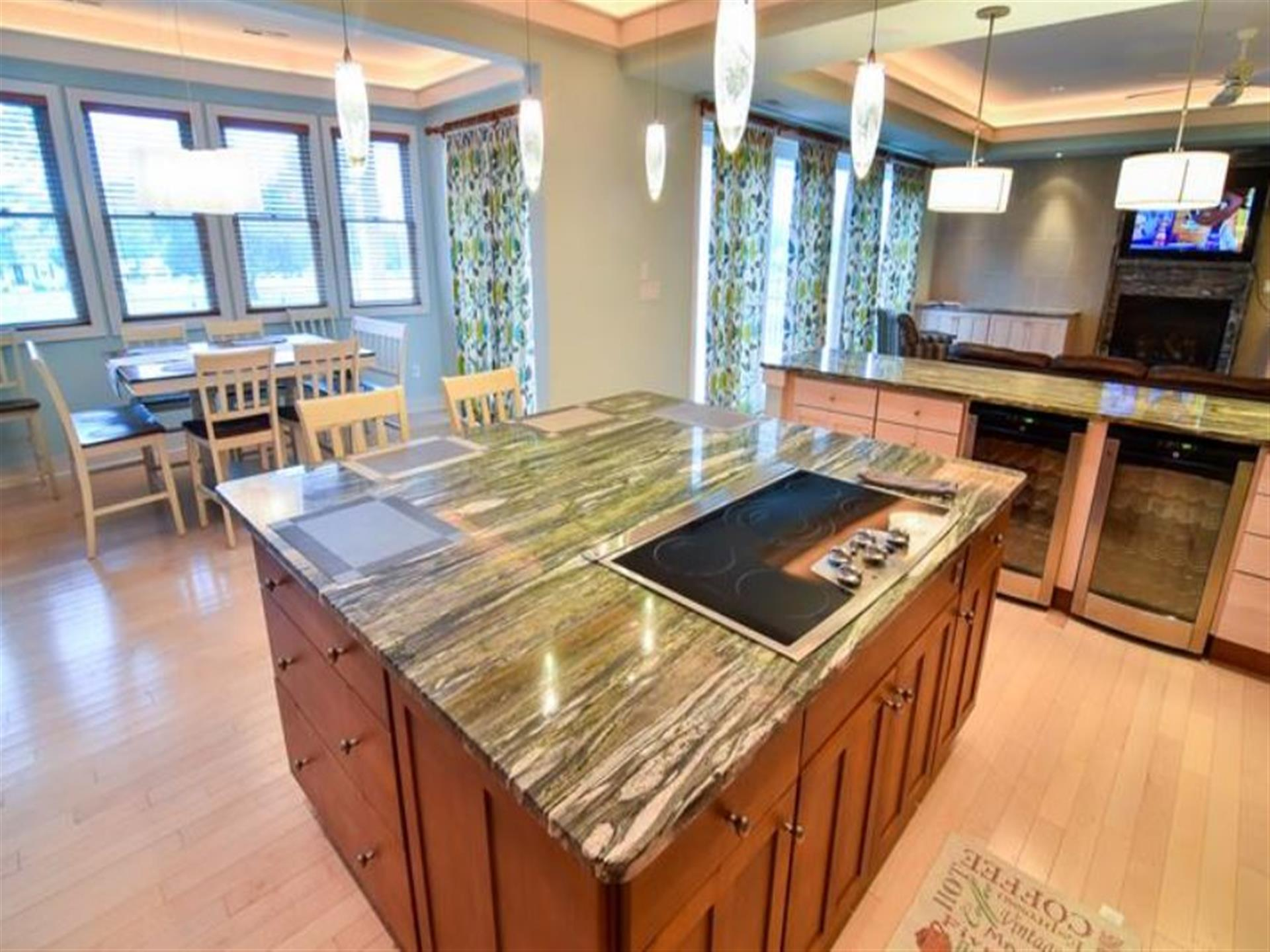 kitchen with middle island, counter with two wine coolers and a kitchen table