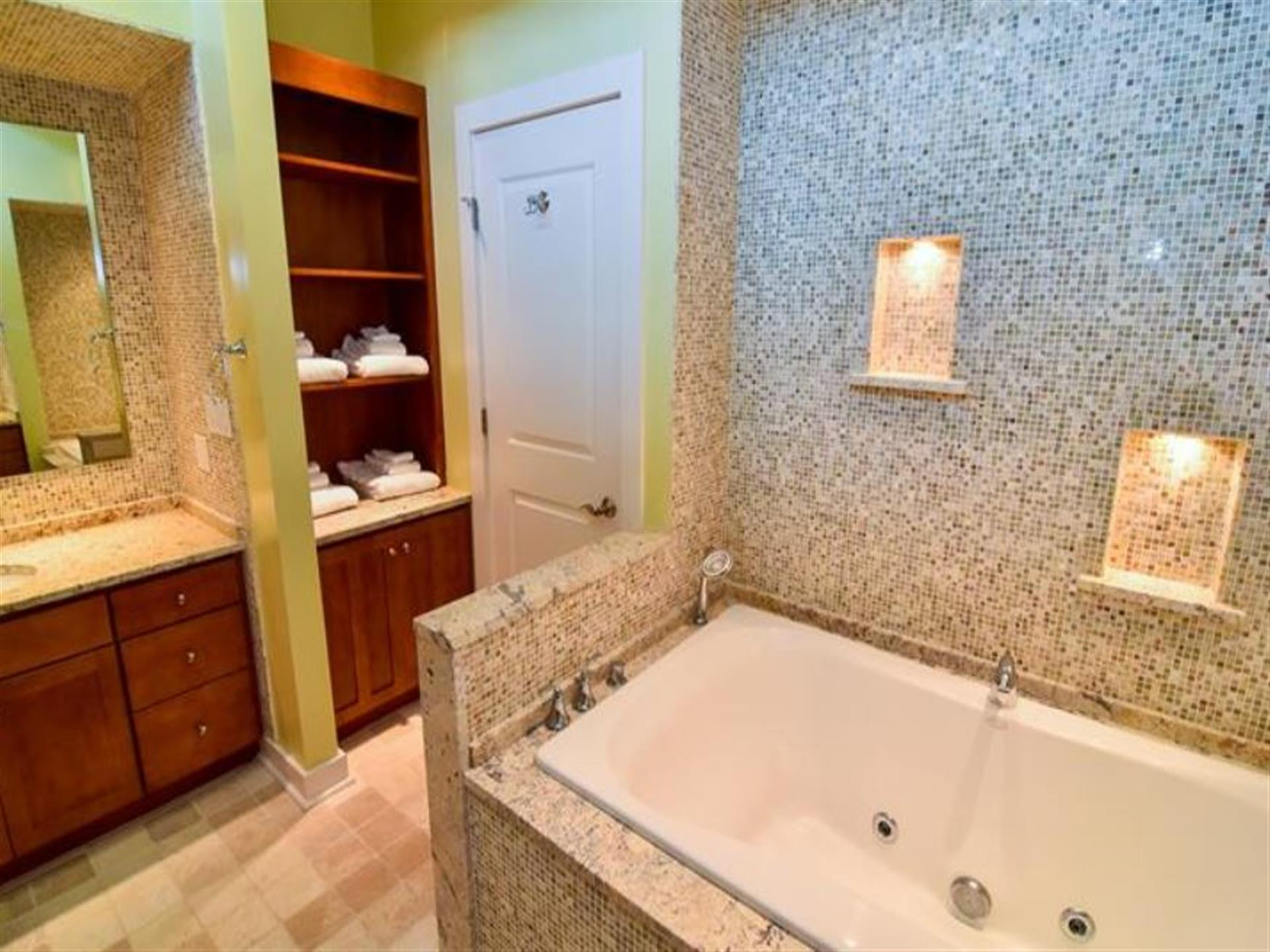 One bathrrom with speckled tiles as well as a tub