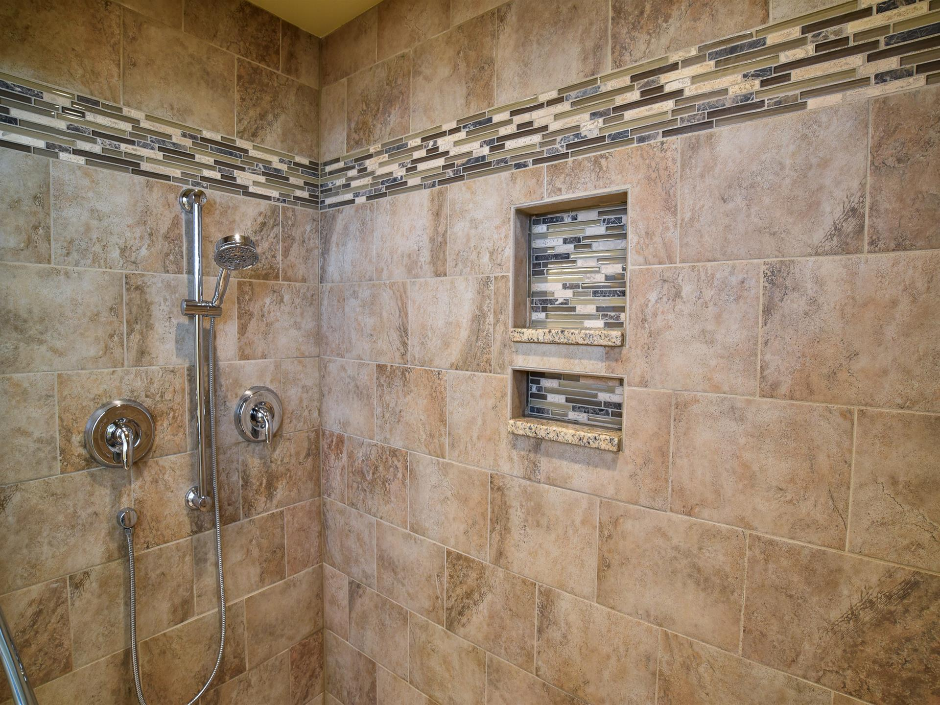 a fancy looking shower area with tiles