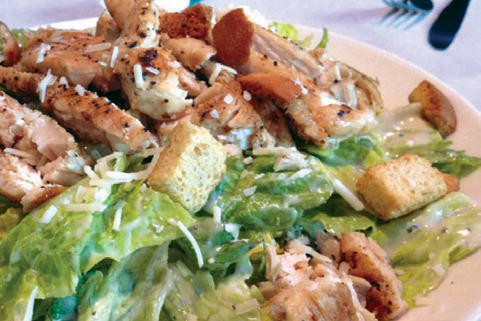 Lettuce salad with chicken and croutons, topped with shredded cheese