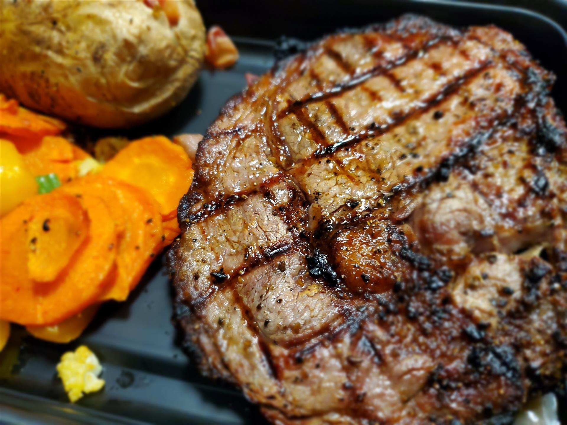 grilled steak with baked potato and roasted veggies