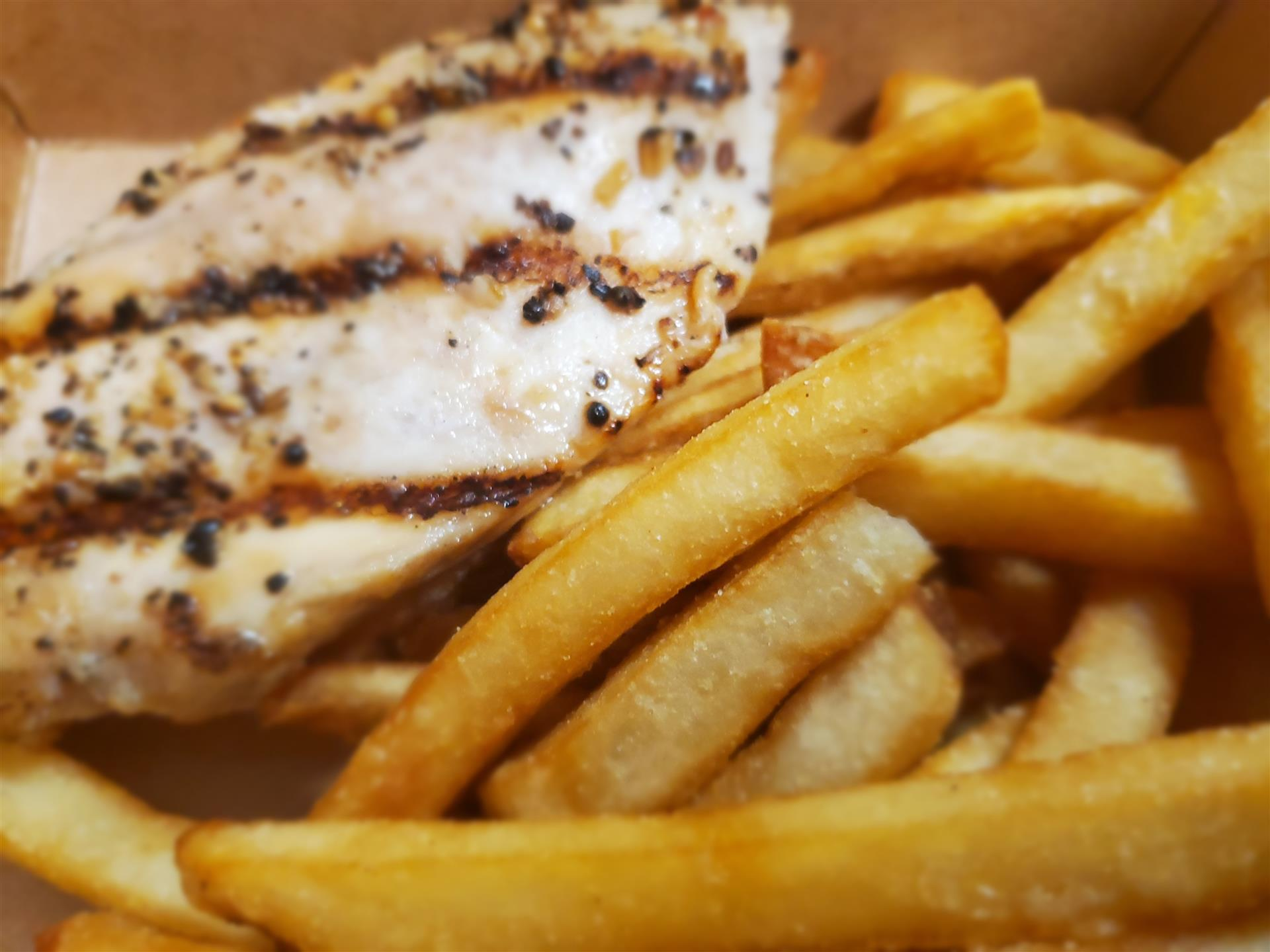 piece of grilled chicken with a side of french fries