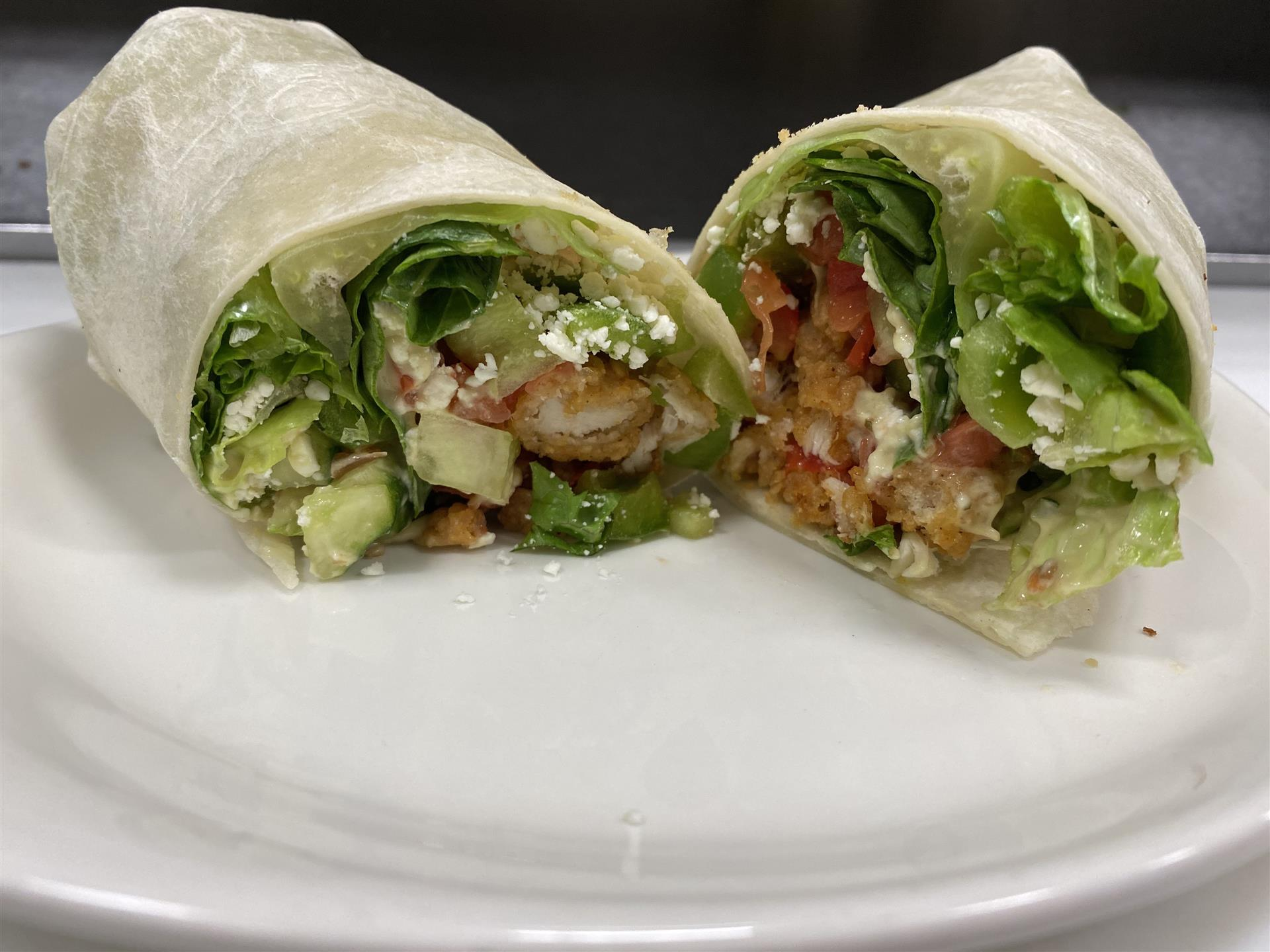 crispy chicken wrap with ranch dressing, tomatoes, lettuce and cheese