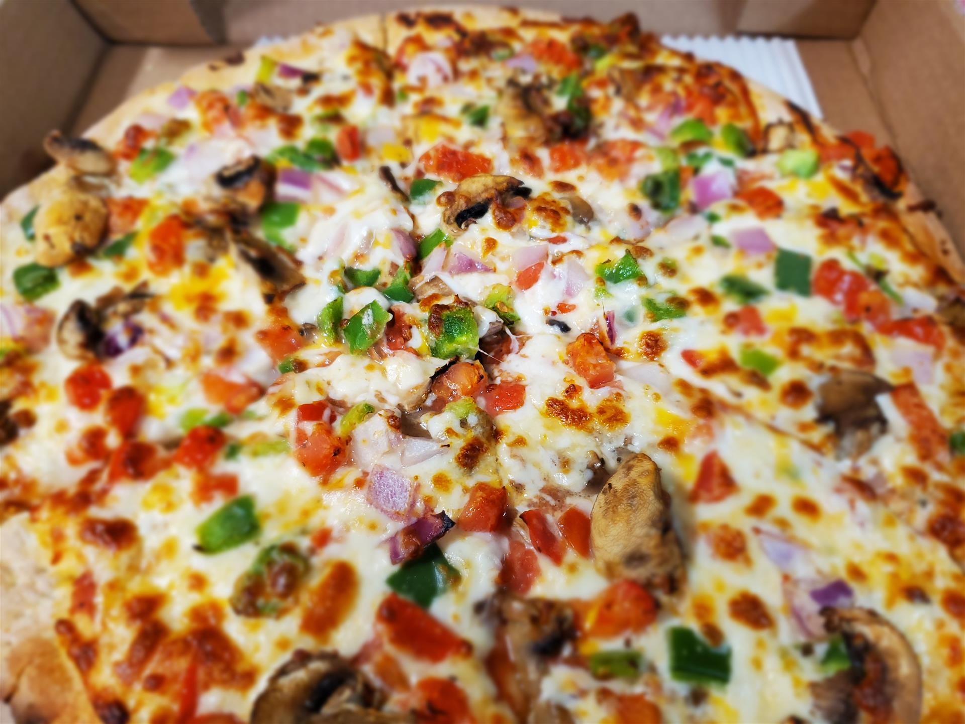 mardi gras pizza- pizza pie with bell peppers, onions, chicken, and tomato
