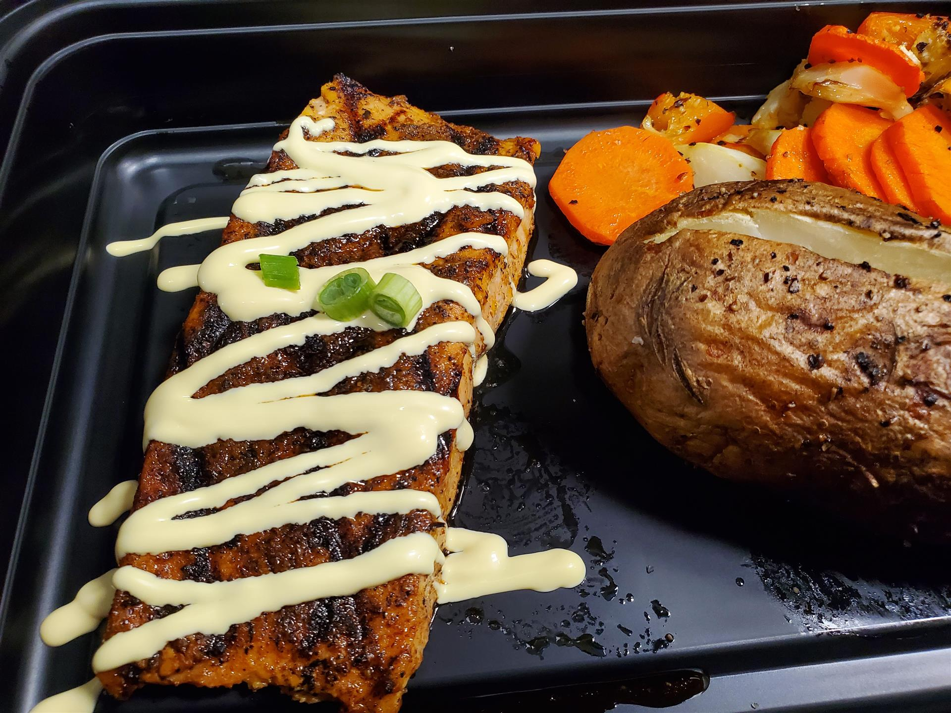 grilled salmon topped with aioli, baked potato and roasted veggies on the side