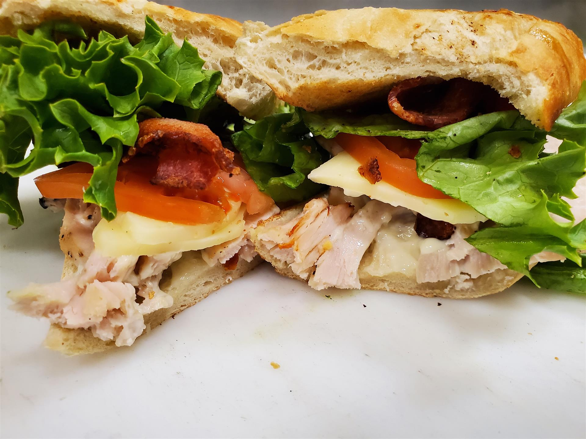 turkey club sandwich with bacon, cheese, lettuce and tomato
