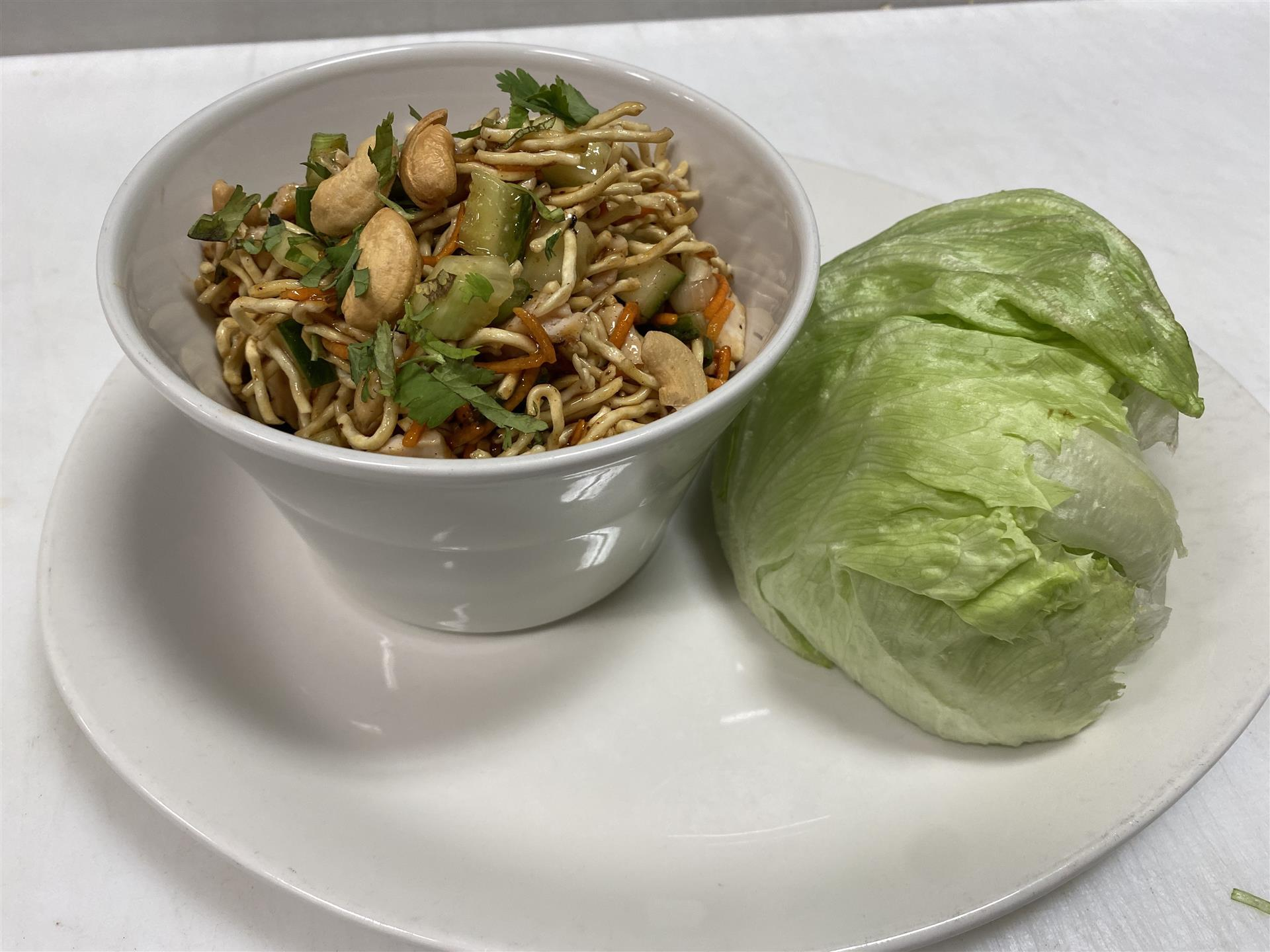 thai lettuce wraps appetizer: half head of iceburg lettuce with cup of lettuce wrap fillings