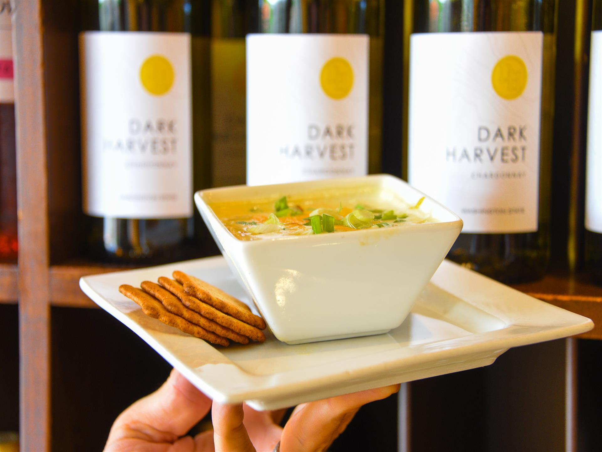 bowl of loaded baked potato soup with three bottles of wine in the backgroun