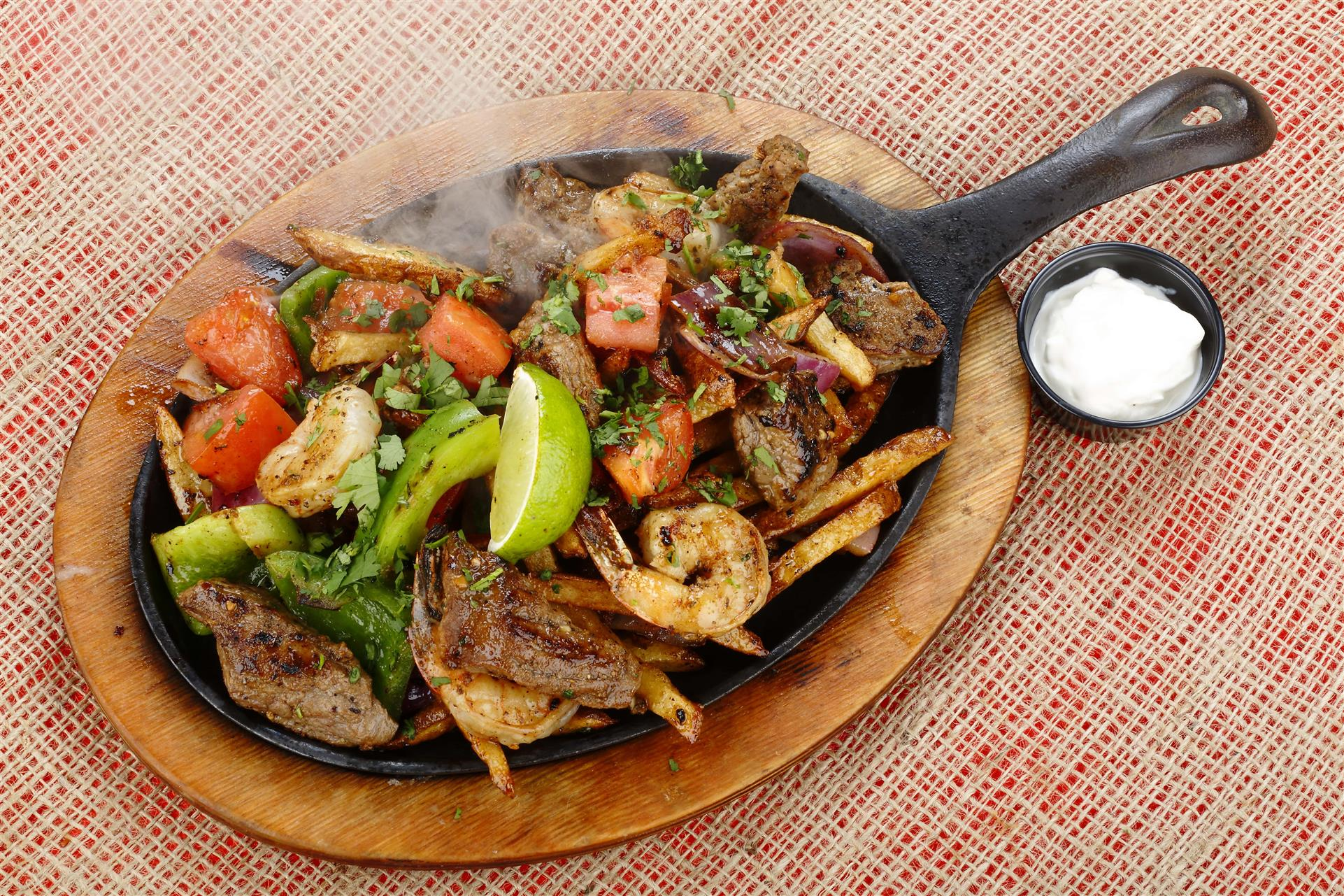 Carne Asada shrimp entree in a skillet with vegetables and lime