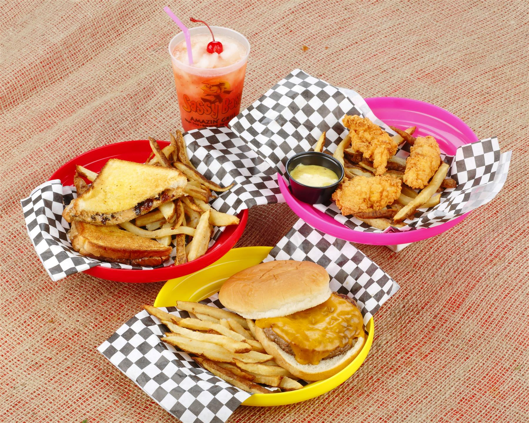 Assorted kids meals in baskets on a wood table with an iced juice drink