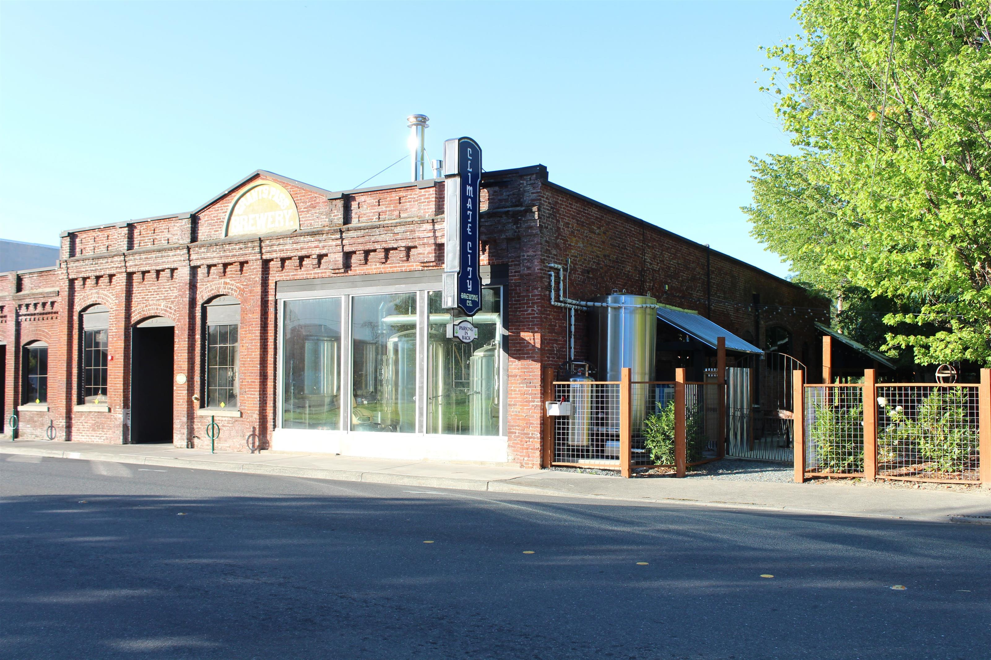 exterior of Climate City Brewing Company with a parking lot in front and a side patio area