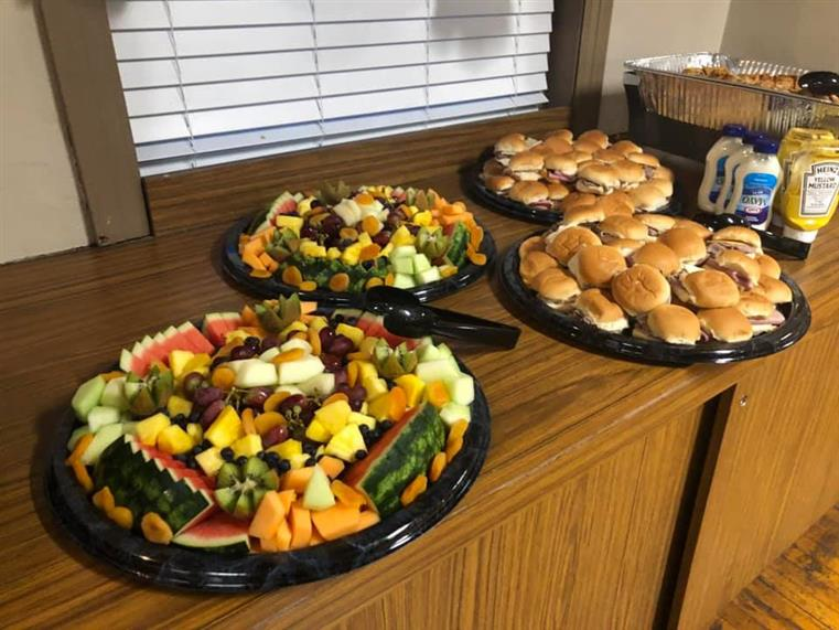 catering platters on a counter of various sandwiches on rolls, fruits and condiments