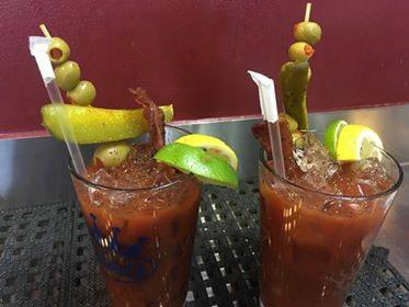 two glasses of bloody marys both with skewers of olives and pickles