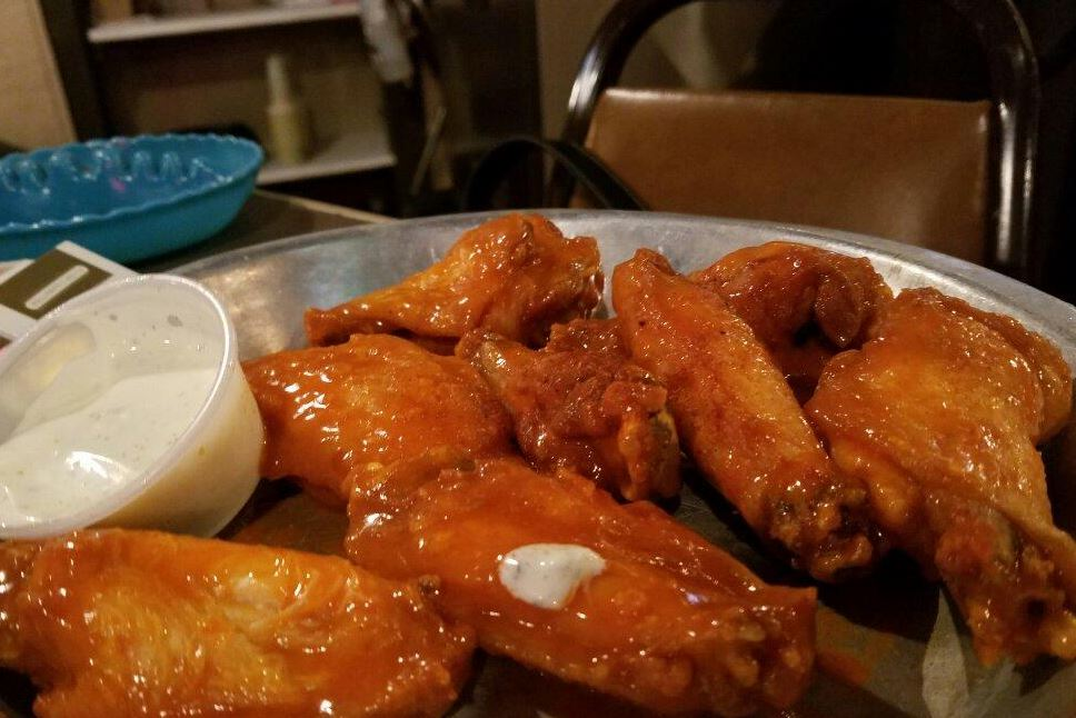 plate of buffalo wings in sauce with a side of dipping sauce