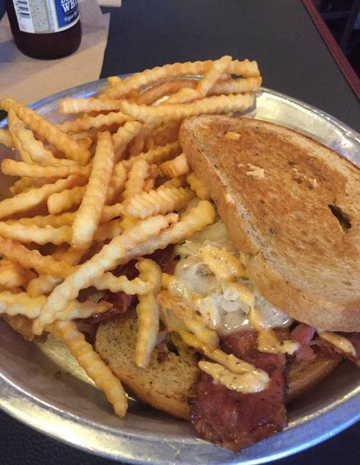 corned beef sandwich with mustard and a side of french fries