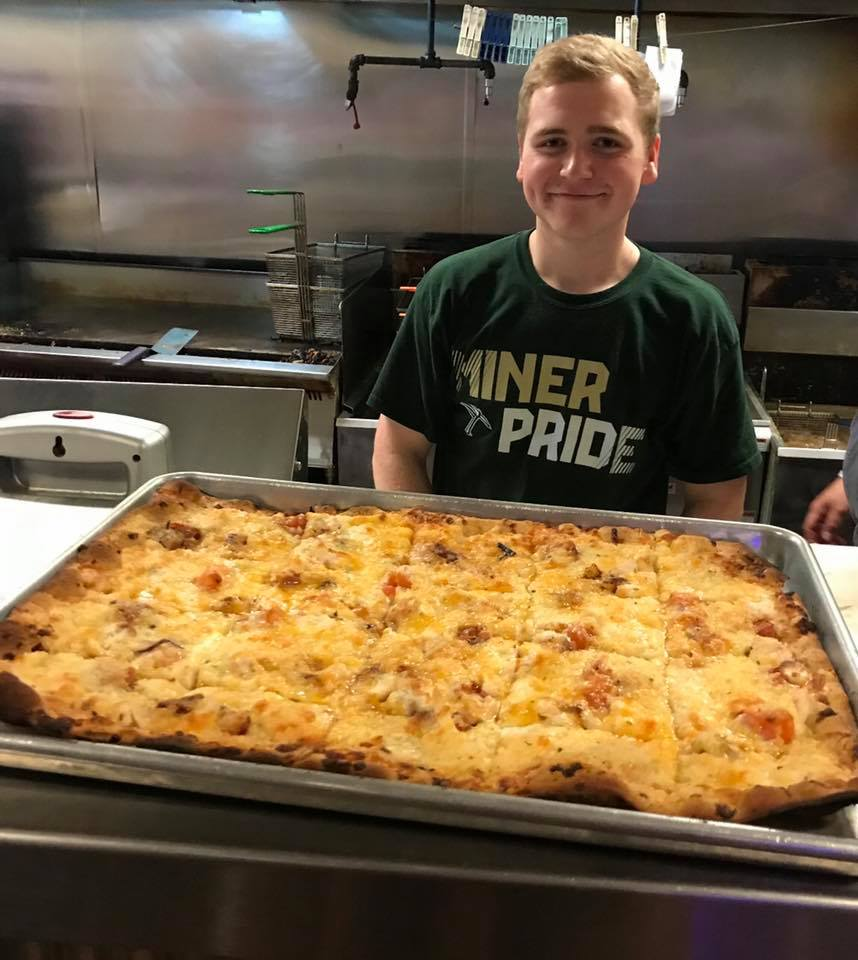 chef smiling behind a large cheese pizza on a counter