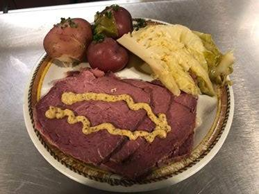 corned beef and cabbage with cooked potatoes on the side
