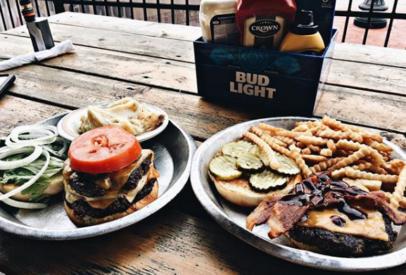 two separate plates on a table outdoors with cheeseburgers topped with pickles and bacon and a side of french fries