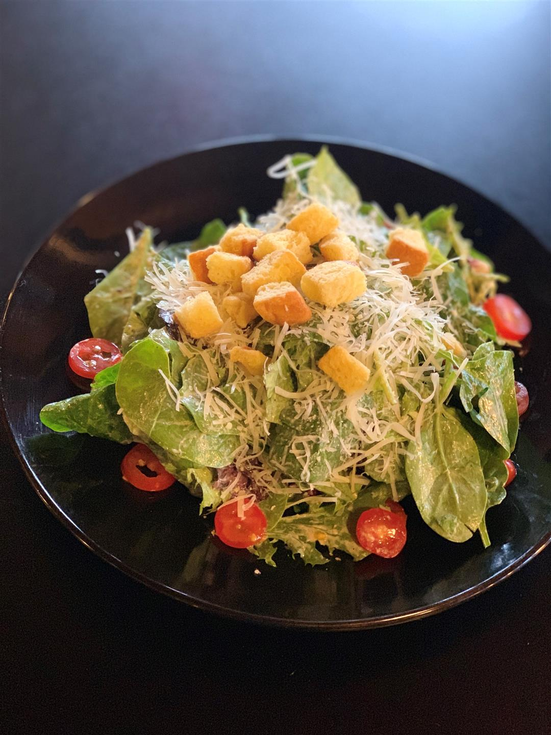 caesar salad with shredded parmesean cheese, croutons and tomatoes