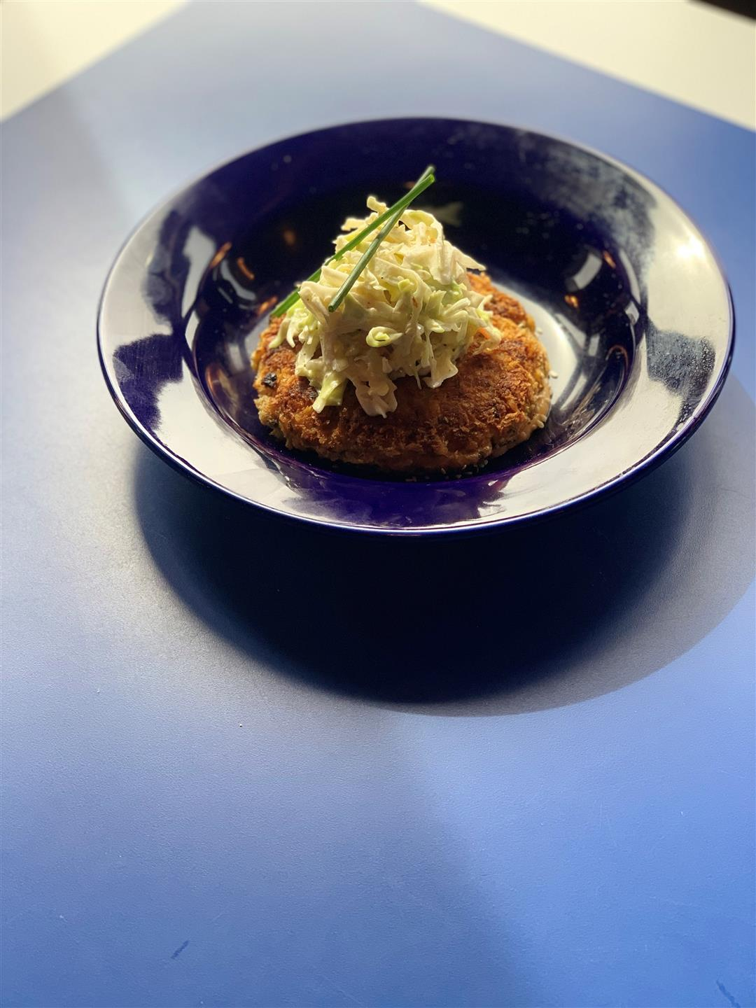 crab cake served with coleslaw on top