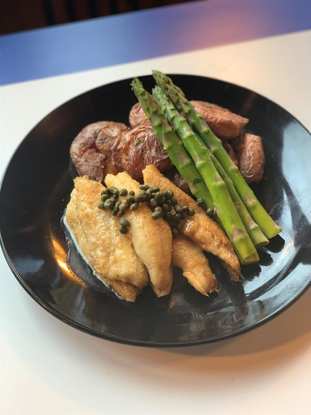 fried perch topped with capers and served with potatoes and asparagus