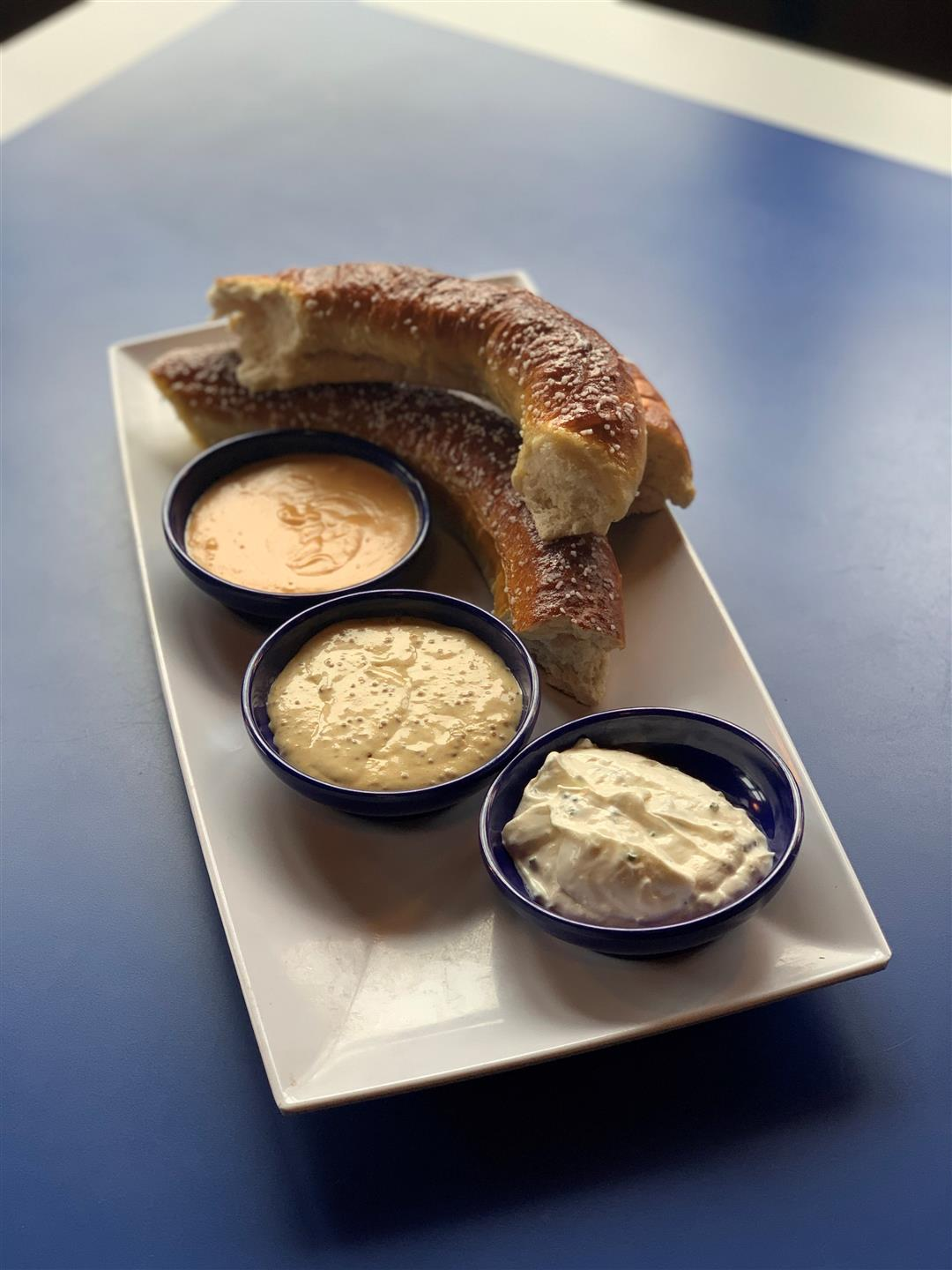 hot pretzel pieces served with cheese sauces and different mustards