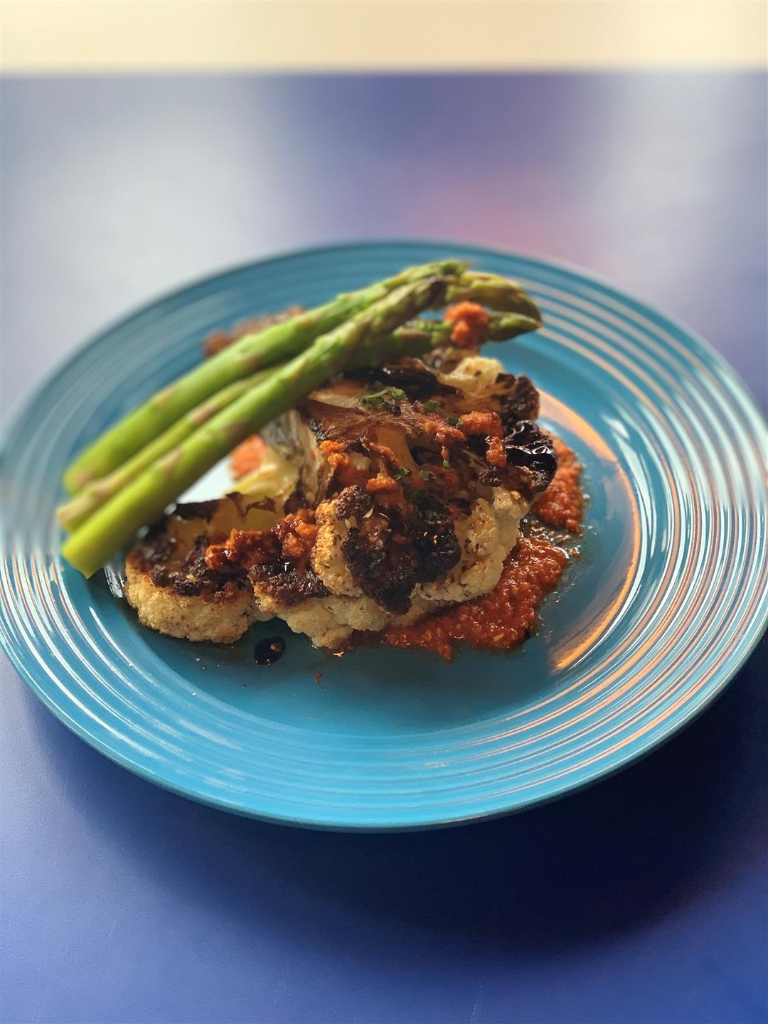 vegan cauliflower 'steak' served with asparagus