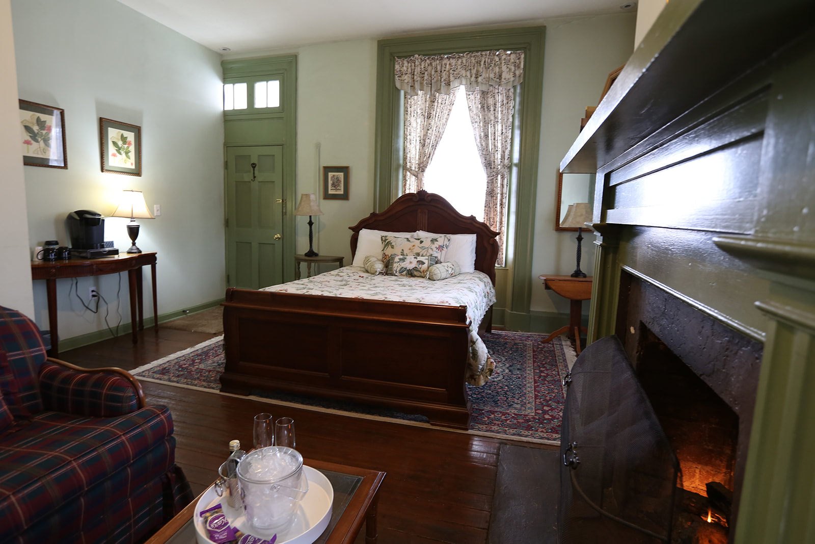 the Monroe Suite room with a bed, fireplace, couch, lamps and a keurig machine