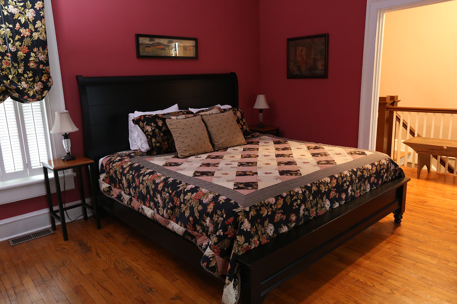 Red walls with queen size bed and black, red, and white quilt bedding with black head board