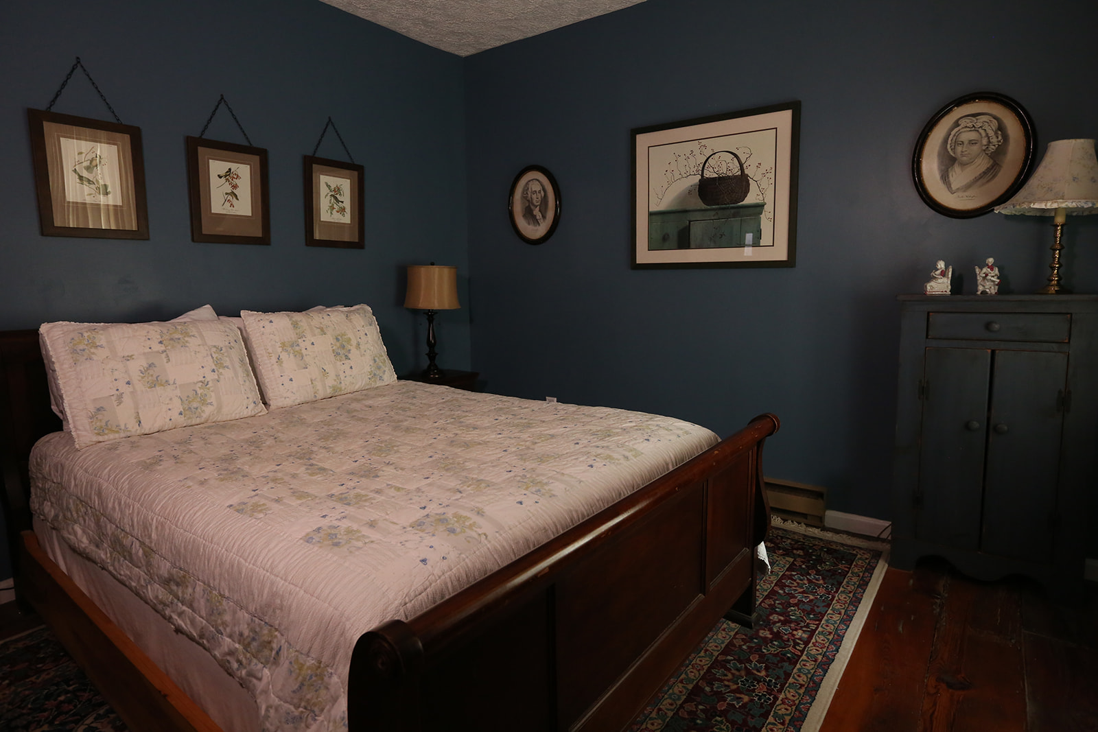 the Washington Suite room with a bed, picture frames on the walls and a dresser