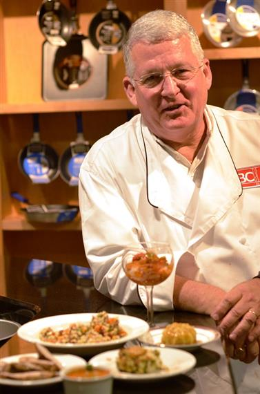 Chef Alan Pyles posing next to a few plate entrees with a cabinet behind him with metal pans hanging down