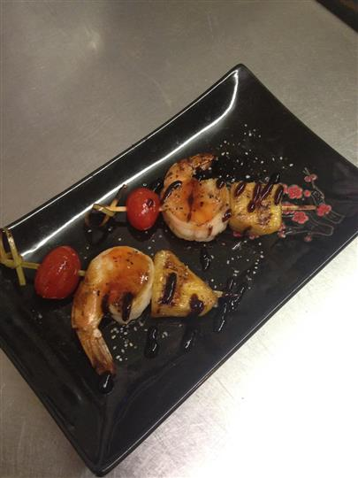 Grilled skewered shrimp, pineapple, cherry tomato on dish