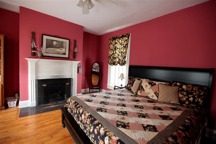 King sized bed in room with wood floors, fireplace, mirror in corner