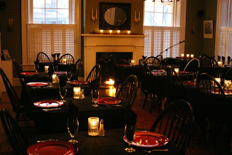 Dining room with placesettings on candle-lit clothed tables.