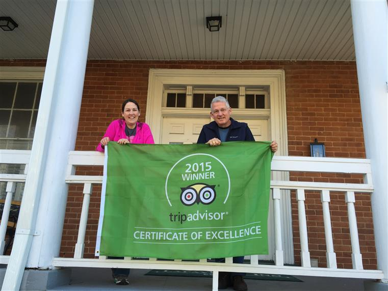 Kaye and Alan on balcony holding trip advisor 2015 winner of certificate of excellence banner.