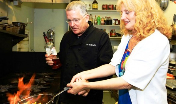 Chef Alan and woman cooking over an open flame in a kitchen