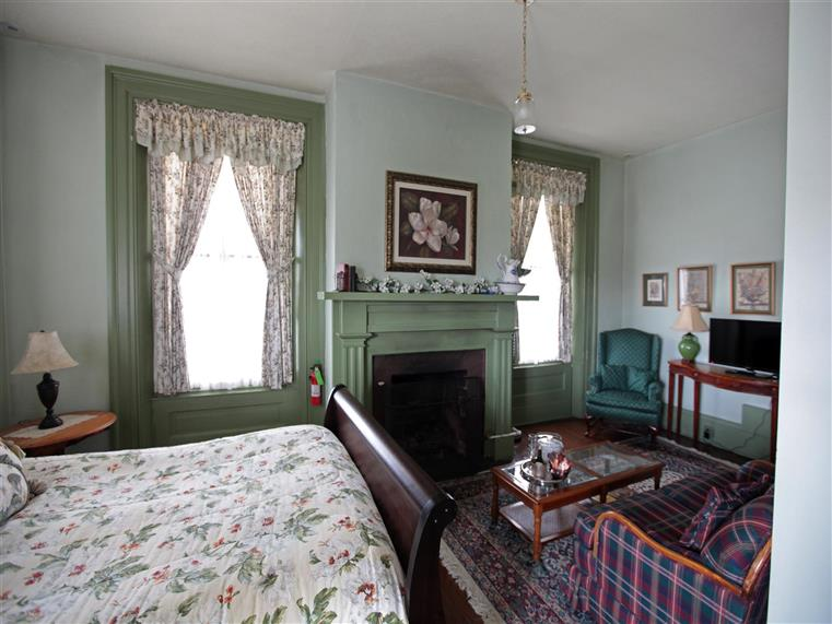 Room with bed, fireplace, couch, coffee table, chair in corner