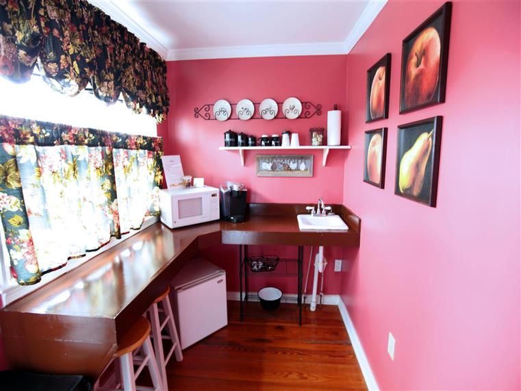Room with counter, stools, mini fridge, sink, fruit photographs framed on walls.