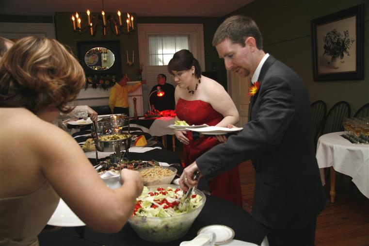 wedding guests together at a catering buffet station placing food onto their plates