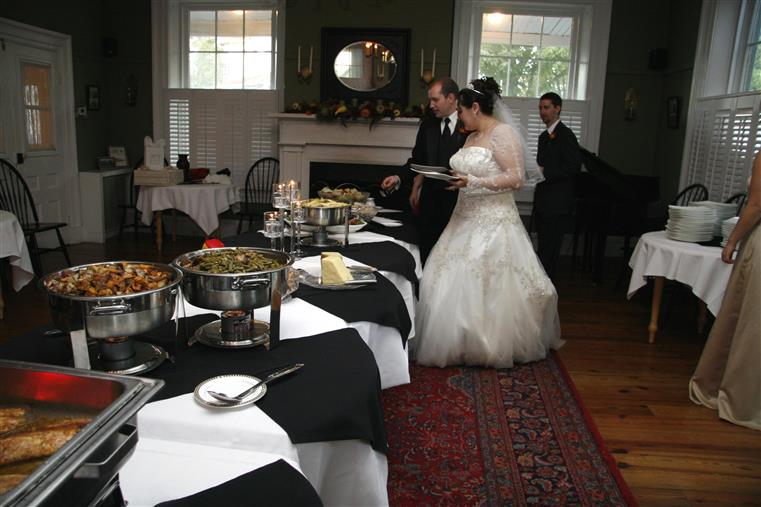 bride and groom at a catering buffet station placing food onto their plates