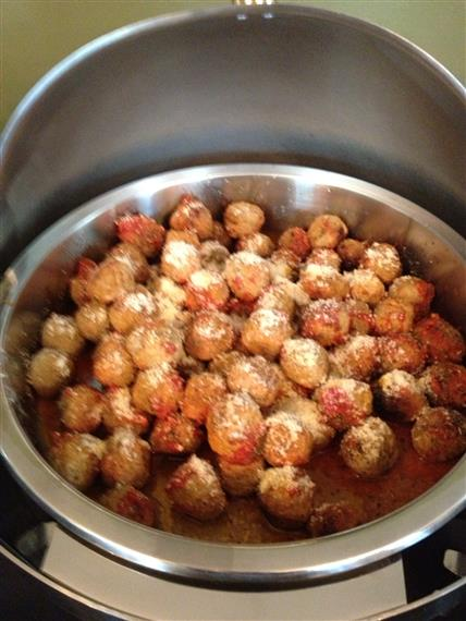 metal sternos filled with meatballs in sauce with grated cheese